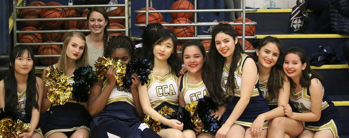 christian academy, cheerleaders, sit together, smiling