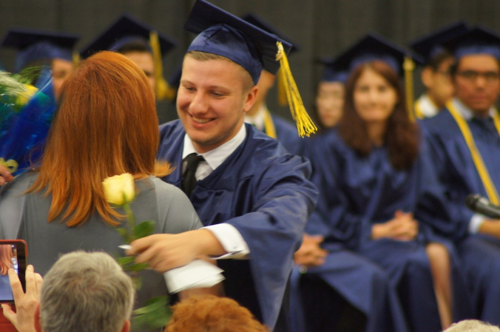 Graduating senior gives his mother a flower