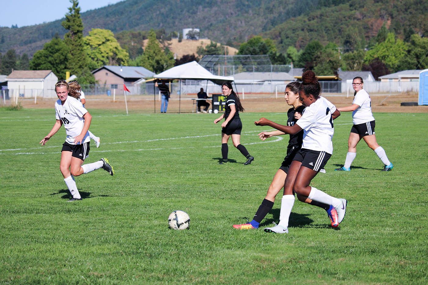 American boarding school, fall sports, include girls' soccer, player runs next to opposing player, to take soccer ball