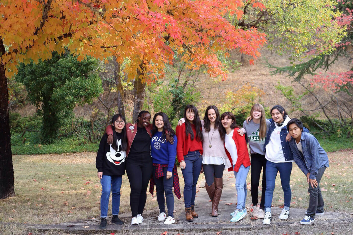 Christian boarding school's, after school club, social media group, stand under, a tree with changing leaves, of orange and red, for the fall season