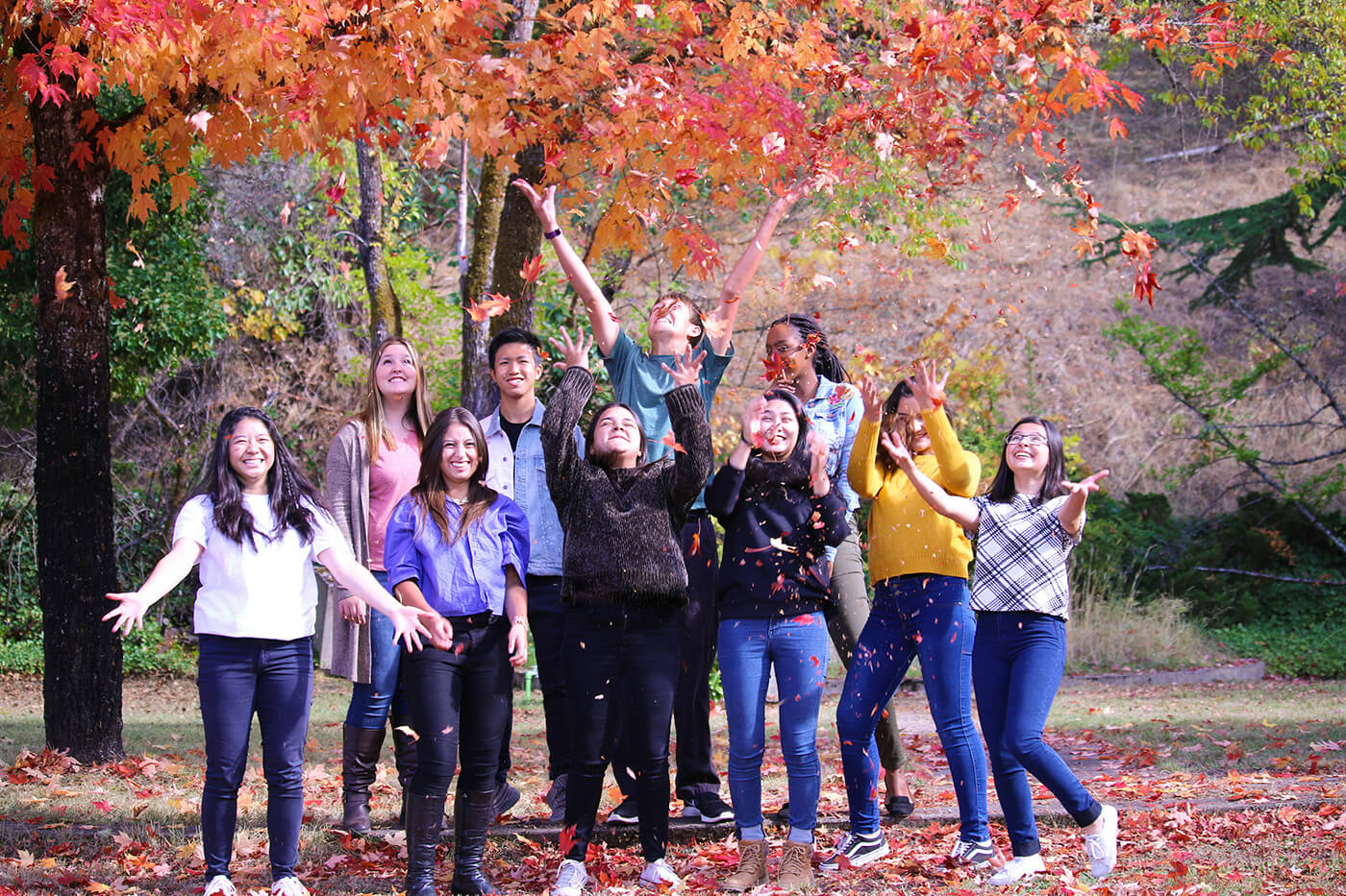 International students, at christian boarding school, enjoy the fall season, by throwing leaves, in the air, that have changed colors