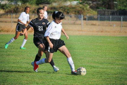 Top Christian Boarding School, fall athletics, girl soccer program, has player, dribbles ball away from opposing team player