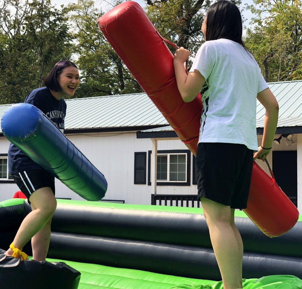 Two students enjoying a round of joust, at college preparatory high school, Canyonville Academy
