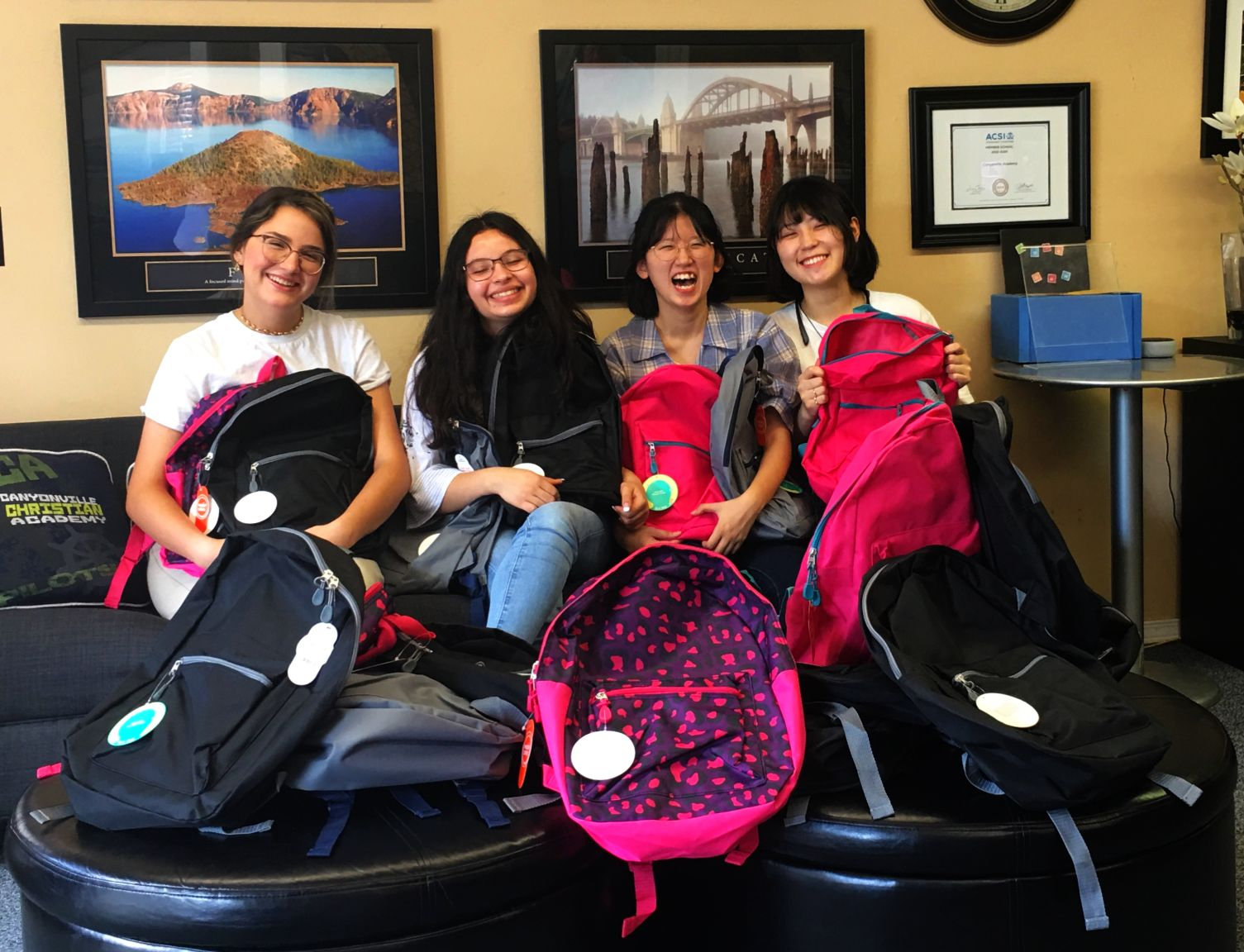 Four Canyonville Academy students pose with the backpacks filled with supplies to be donated to local schools