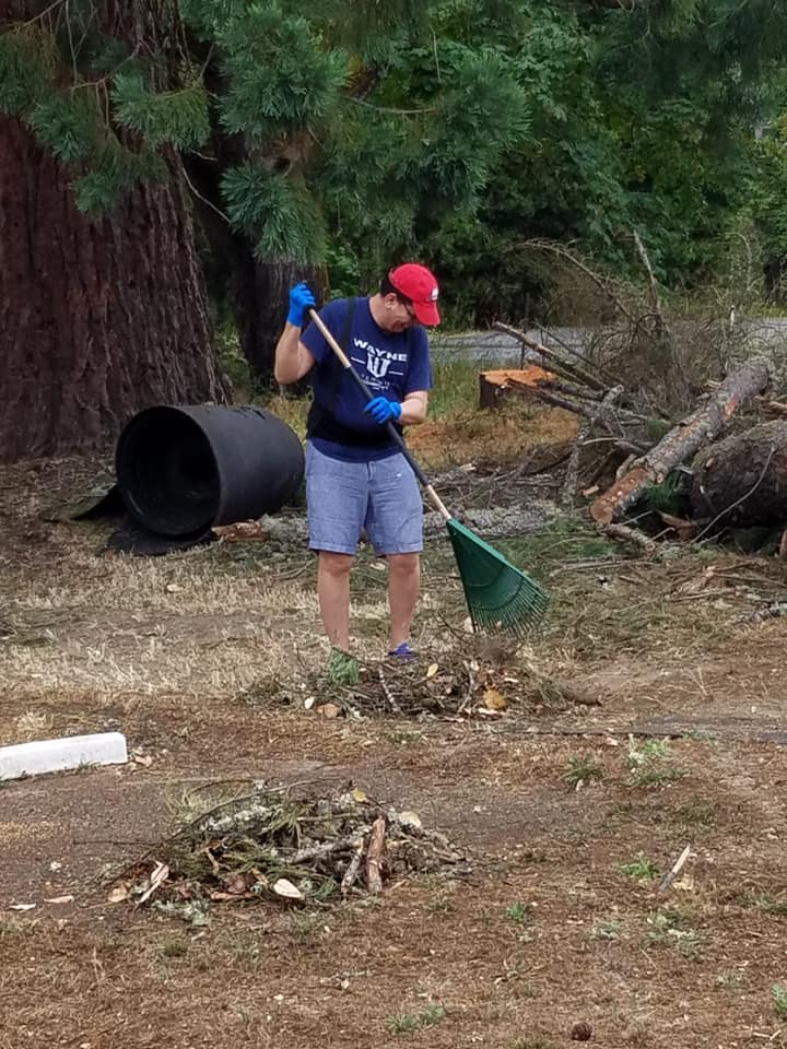 Volunteers cleaning up the debris from fallen trees.